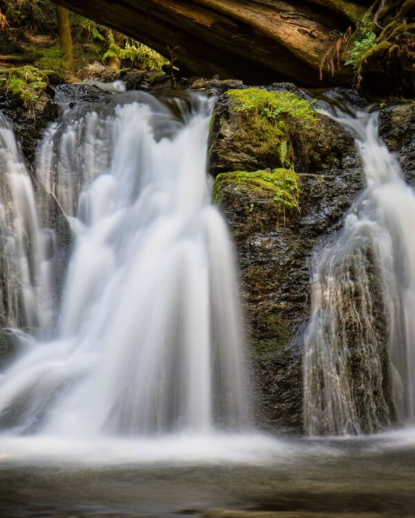 two waterfalls flowing into dark river