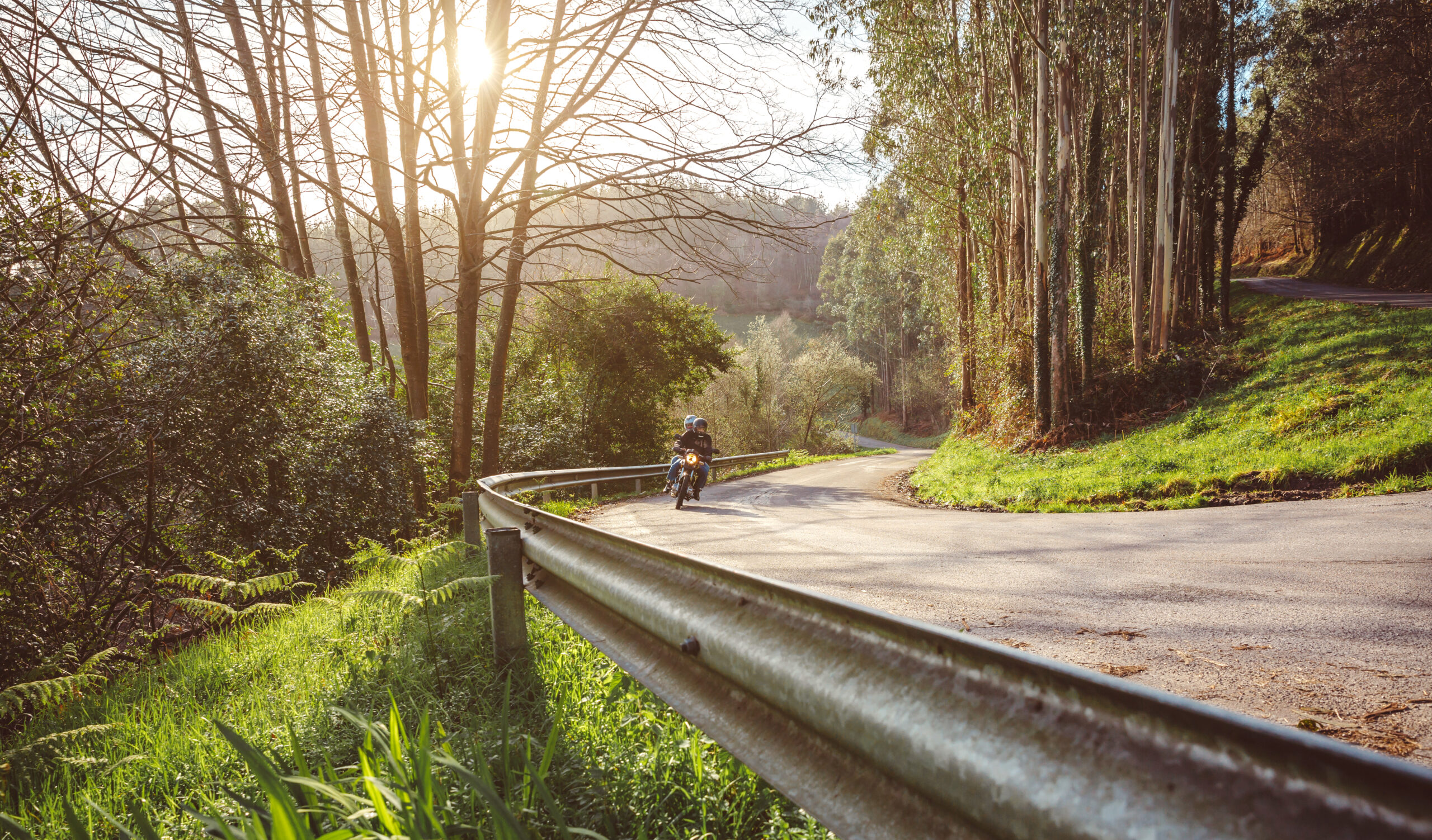 Senior couple riding motorbike along forest road