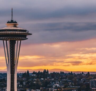 Seattle space needle in foreground with orange purple sunset in background