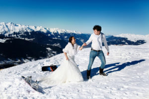 a couple getting married on the top of a snowy mountain